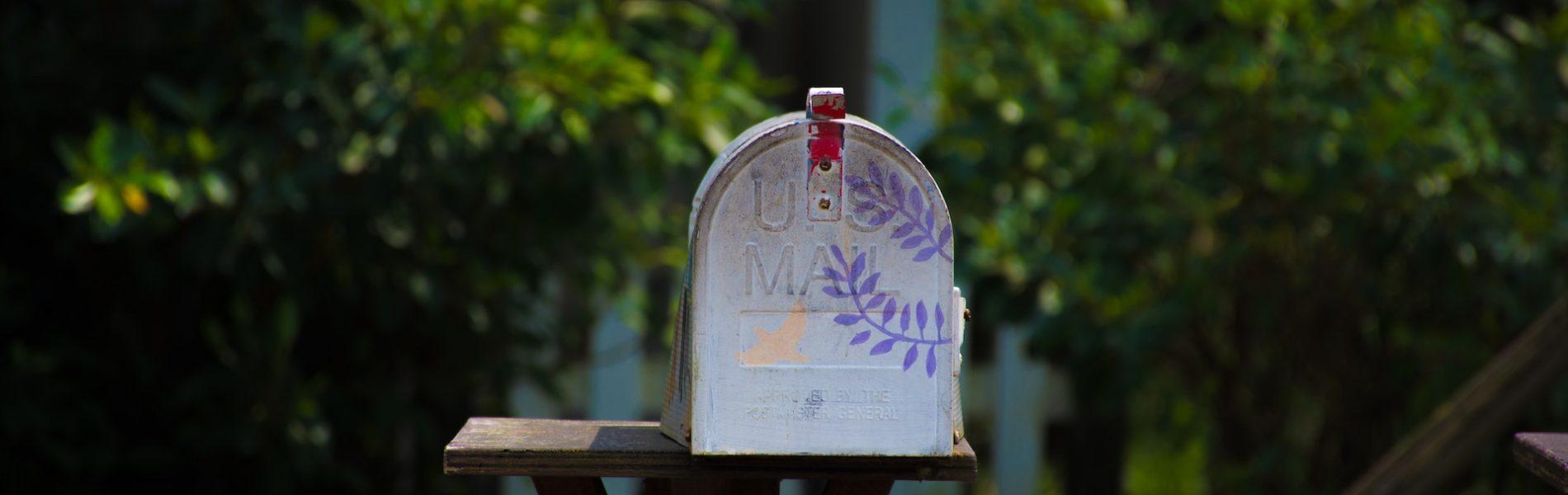 Photo d'une vieille boite aux lettres en métal avec des branches violette dessinées sur le devant
